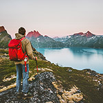 Discoverer tourist man trekking in sunset mountains Traveling lifestyle adventure concept hiking with red backpack wanderlust vacations outdoor