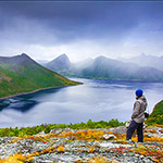 One tourist look at beautiful fjord. Spring northern landscape. Senja island, Norway.