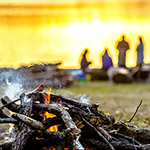 Group of friends on camp with campfire and sausages grilling over fire and smoke